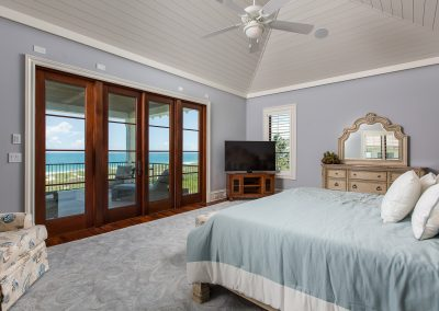 View of ocean through would windows and doors in guest bedroom